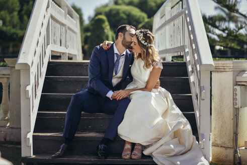 Bridal couple sitting on stairs enjoying their wedding day - JSMF00576