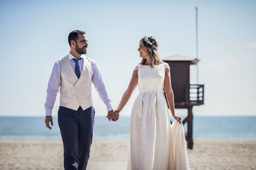 Happy bridal couple walking hand in hand on the beach - JSMF00585