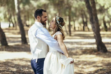 Happy bridal couple dancing together in pine forest - JSMF00588
