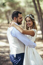 Portrait of happy bride dancing with her groom in pine forest - JSMF00591