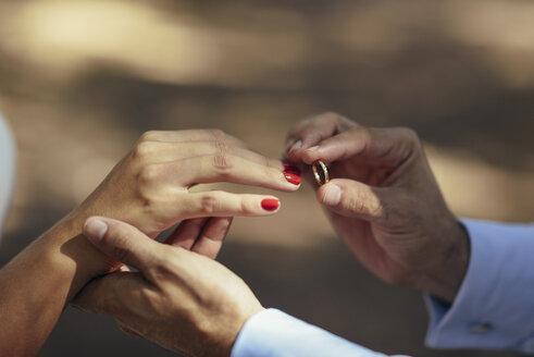 Groom putting wedding ring on finger of bride, close up - JSMF00594