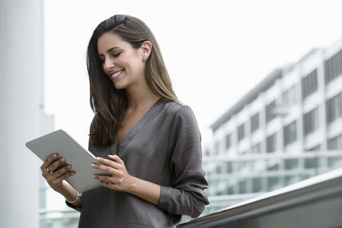 Smiling young businesswoman using digital tablet outdoors - BMOF00077