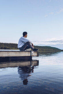 Young man sitting at lake Inari, looking at view, Finland - RSGF00096