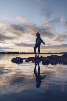 Young woman standing at lake Inari, with arms outstretched, Finland - RSGF00099
