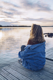 Young woman sitting at lake Inari, looking at view, Finland - RSGF00102