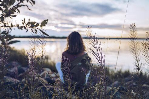 Young woman sitting at lake Inari, looking at view, Finland - RSGF00105