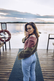 Pretty young woman posing on a pier at Lake Inari, Finland - RSGF00108
