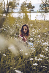 Young woman crouching in flower meadow - RSGF00114