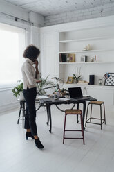 Freelancer standing in her home office, thinking - BOYF00890