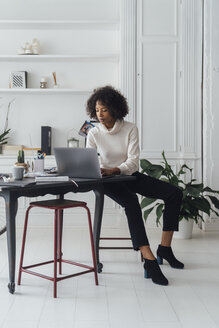 Mid adult woman working in her home office, using laptop - BOYF00893
