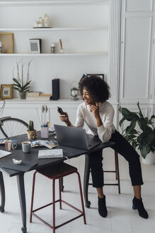 Mid adult woman working in her home office, using smartphone - BOYF00902