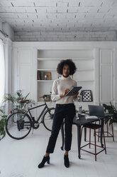 Mid adult freelancer standing in her home office, using digital tablet - BOYF00908