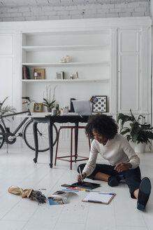 Disigner sitting on ground of her home office, using digital tablet - BOYF00911