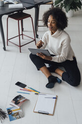 Disigner sitting on ground of her home office, using digital tablet - BOYF00914