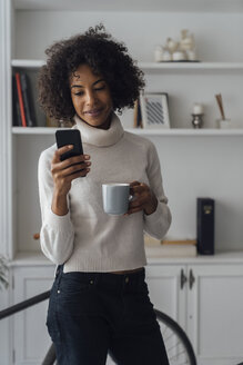 Mid adult freelancer standing in her home office, using smartphone, holding coffee cup - BOYF00923
