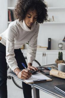 Freelancer standing at hert desk, using calculater, taking notes - BOYF00929
