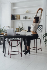 Mid adult woman sitting in her home office, smiling and stretching - BOYF00938