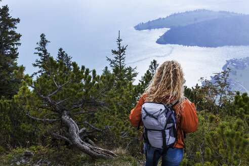 Young woman hiking in the Bavarian mountains, looking at Lake Walchensee - TCF05906
