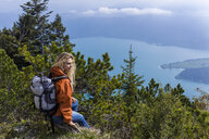 Young woman hiking in the Bavarian mountains, looking at Lake Walchensee - TCF05909