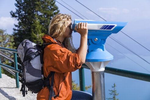 Young woman looking at mountains, using coin operated telescope - TCF05912
