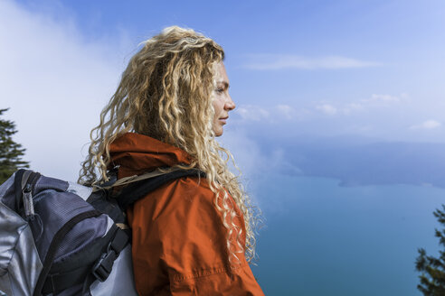 Young woman hiking in the Bavarian mountains, looking at Lake Walchensee - TCF05915