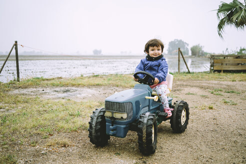 Baby girl driving a toy tractor next to the rice fields - GEMF02500