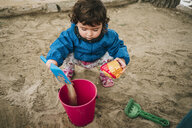 Baby girl playing with sand, shovel and bucket - GEMF02503