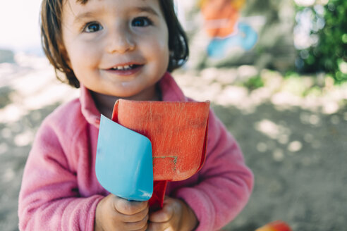Baby girl playing with shovels outdoors - GEMF02509