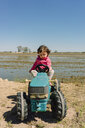 Baby girl driving a toy tractor next to the rice fields - GEMF02512