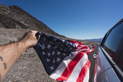 USA, California, Death Valley, man's hand holding American flag besides car - KKAF02955