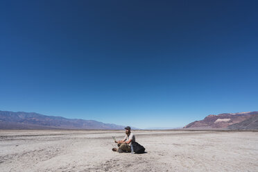 USA, California, Death Valley, man with map sitting on ground in the desert having a rest - KKAF02964