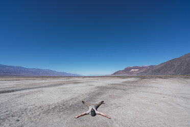 USA, California, Death Valley, man lying on ground in the desert - KKAF02967