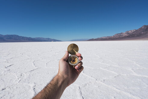 USA, California, Death Valley, man's hand holding compass - KKAF02970