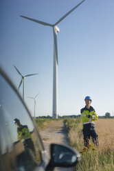 Smiling engineer standing in a field at a wind farm - GUSF01307