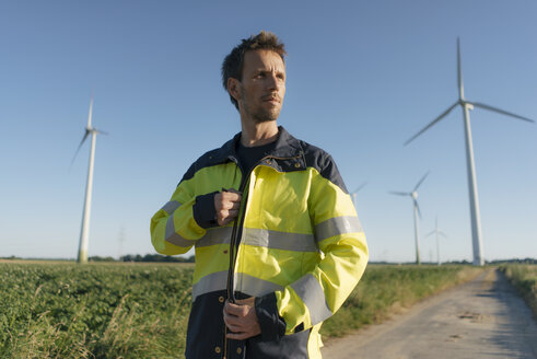 Portrait of an engineer on field path at a wind farm - GUSF01316