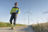 Engineer walking on field path at a wind farm - GUSF01319