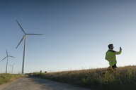 Engineer standing in a field at a wind farm using cell phone - GUSF01325
