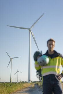 Blurred view of technician standing on field path at a wind farm with climbing equipment - GUSF01328