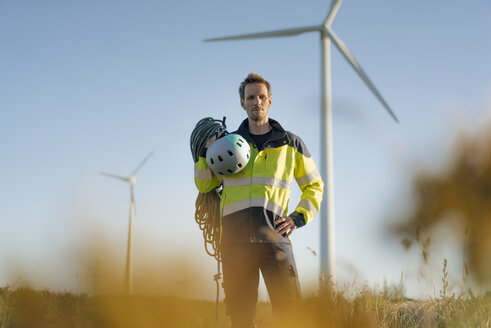 Technician standing in a field at a wind farm with climbing equipment - GUSF01331