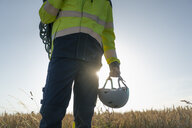 Close-up of technician in a field with climbing equipment - GUSF01334