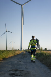 Technician walking on field path at a wind farm with climbing equipment - GUSF01337