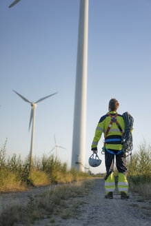 Technician standing on field path at a wind farm with climbing equipment - GUSF01340