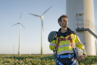 Technician standing at a wind farm with climbing equipment - GUSF01343