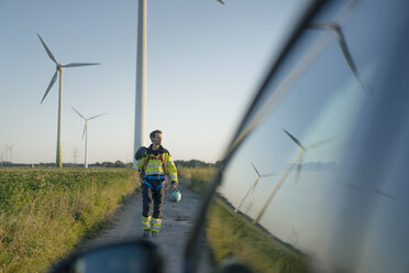 Technician on field path at a wind farm with climbing equipment - GUSF01346