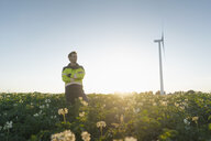 Engineer standing in a field at a wind turbine - GUSF01349