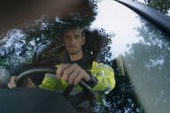 Man in protective workwear driving car - GUSF01358