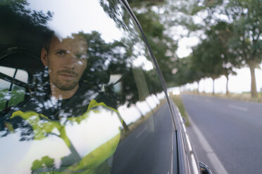 Portrait of man in protective workwear in a car at country road - GUSF01361