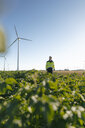 Engineer standing in a field at a wind farm - GUSF01364