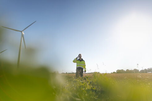 Engineer standing in a field at a wind farm talking on cell phone - GUSF01367