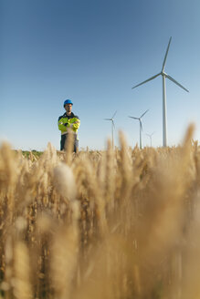 Engineer standing in a field at a wind farm - GUSF01370